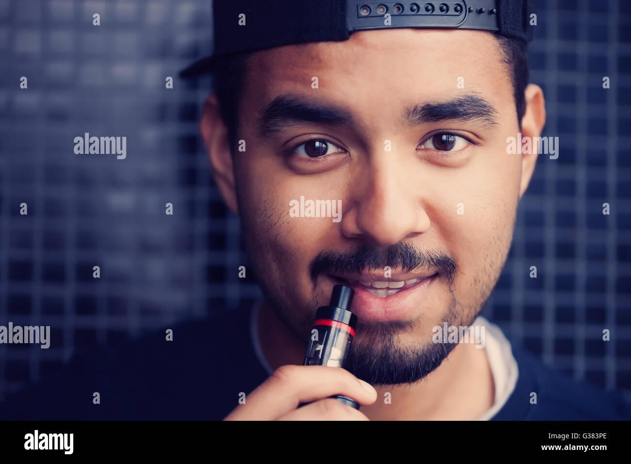 Portrait of smiling young black guy smoking trendy e-cig vaporizer. Popular modern gadget that help quit smoking - Stock Image