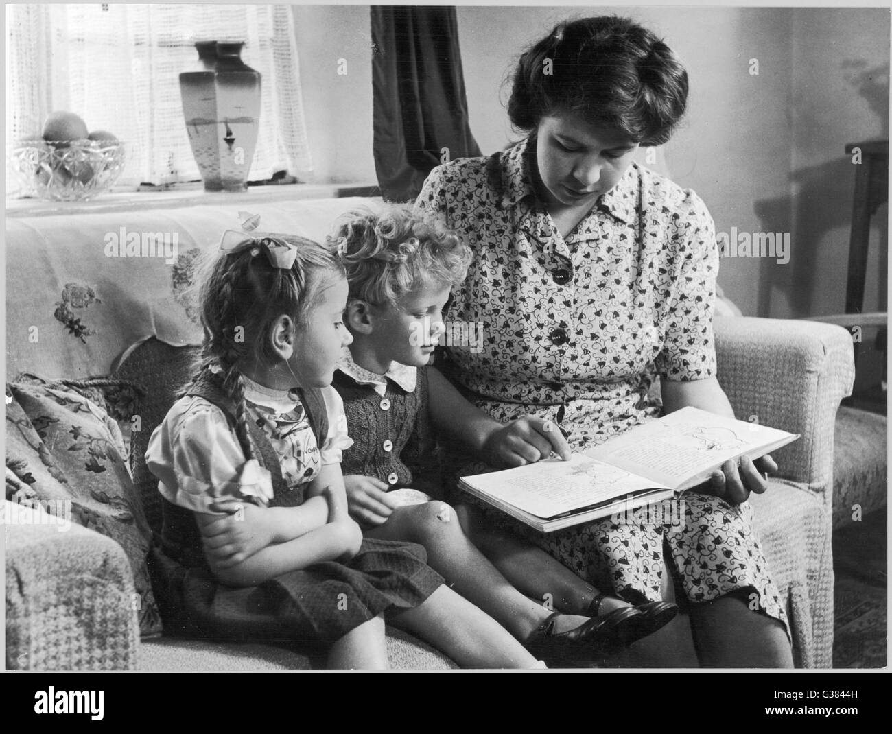 Mother reading a story to her  two children        Date: 1947 - Stock Image