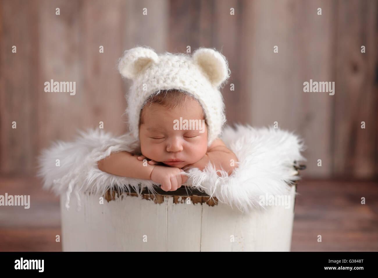An 11 day old newborn baby girl sleeping in a little, wooden bucket. She is  wearing a crocheted, white bear bonnet. Shot in the e81cdfba142