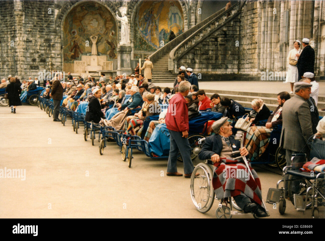 Invalid pilgrims wait  patiently in their wheelchairs  for the afternoon Mass in  front of the Rosary       Date: - Stock Image