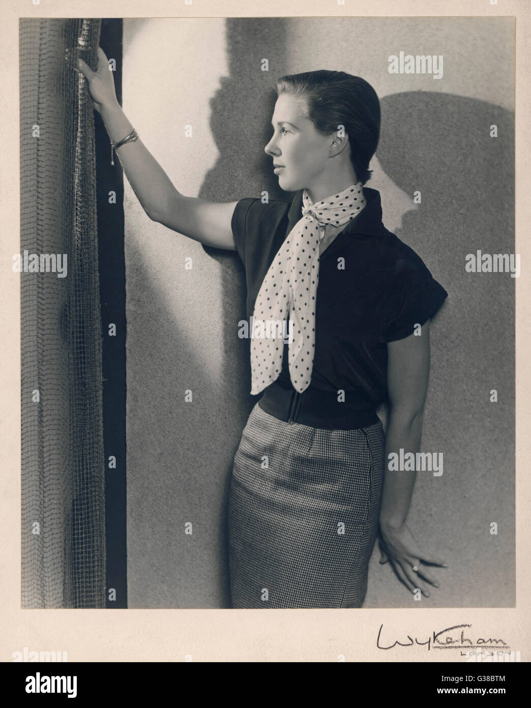 A young woman with a very short  hair-cut, wearing a pencil  skirt, cap-sleeved blouse and  wide elasticated belt Stock Photo