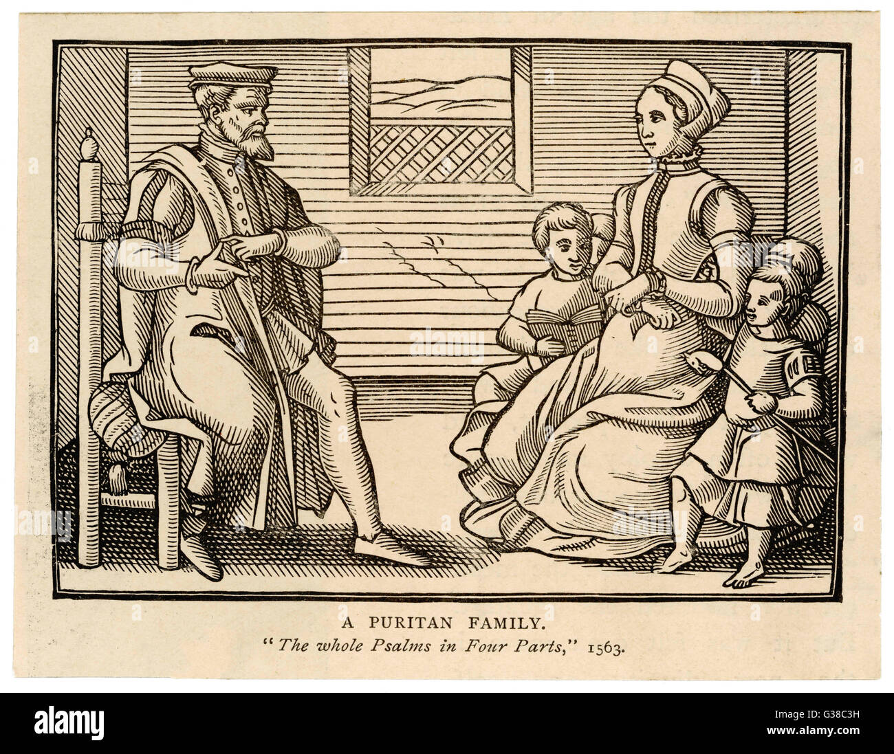 A Puritan family - father sits separately, while his pregnant  wife sits with their 4  children nestled around her. - Stock Image