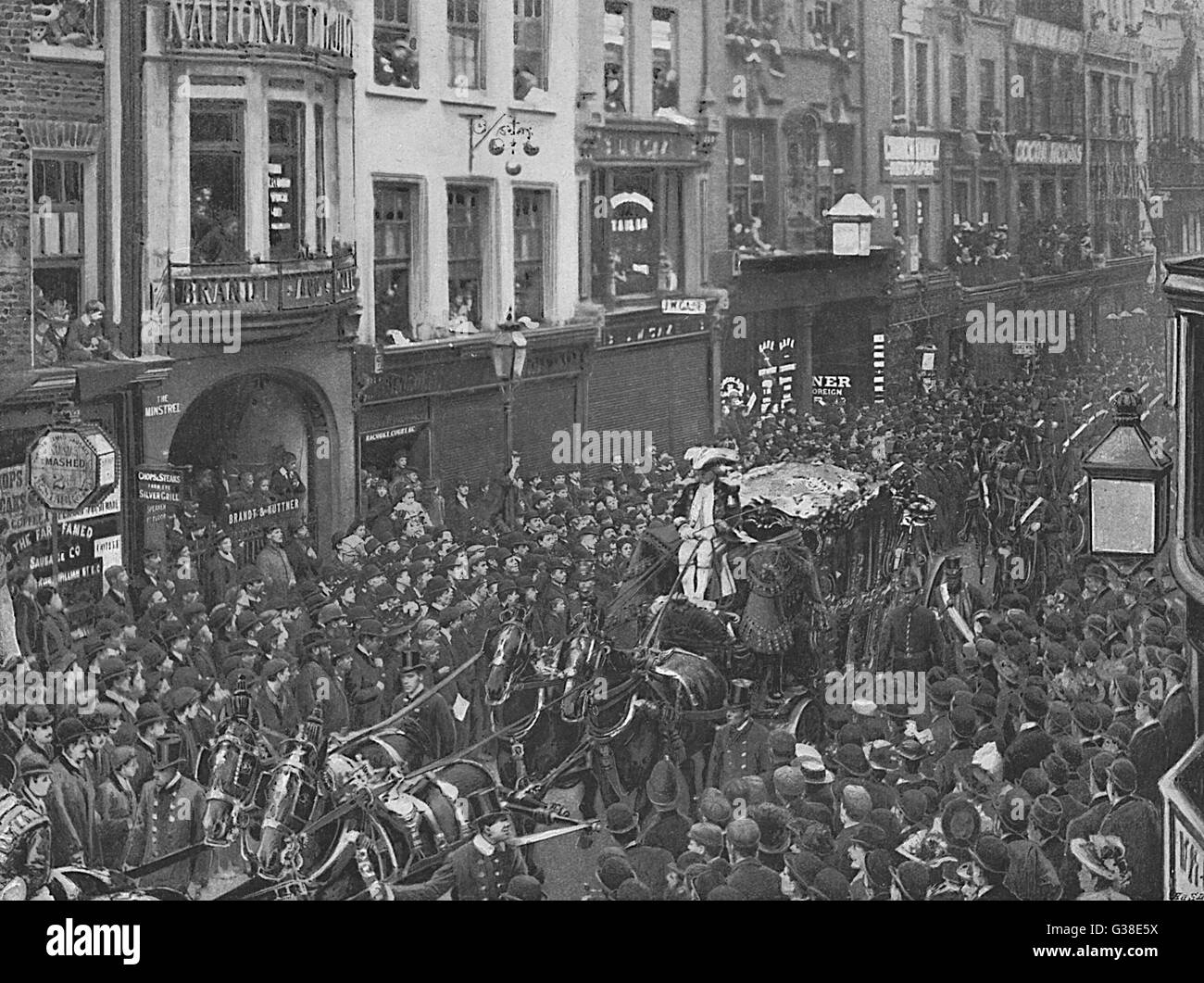 The Lord Mayor's coach passes  through a narrow street of the  City of London, packed with  enthusiastic crowds - Stock Image