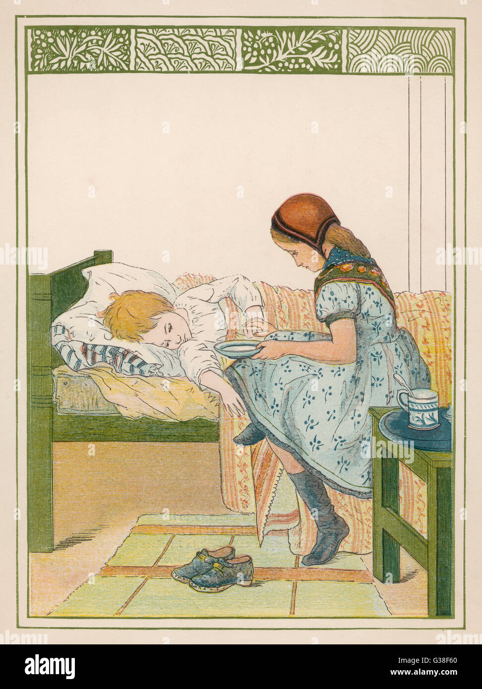 CLOGS  A young girl acting as nurse  has removed her clogs and sits  on the edge of the sickbed  while she offers - Stock Image