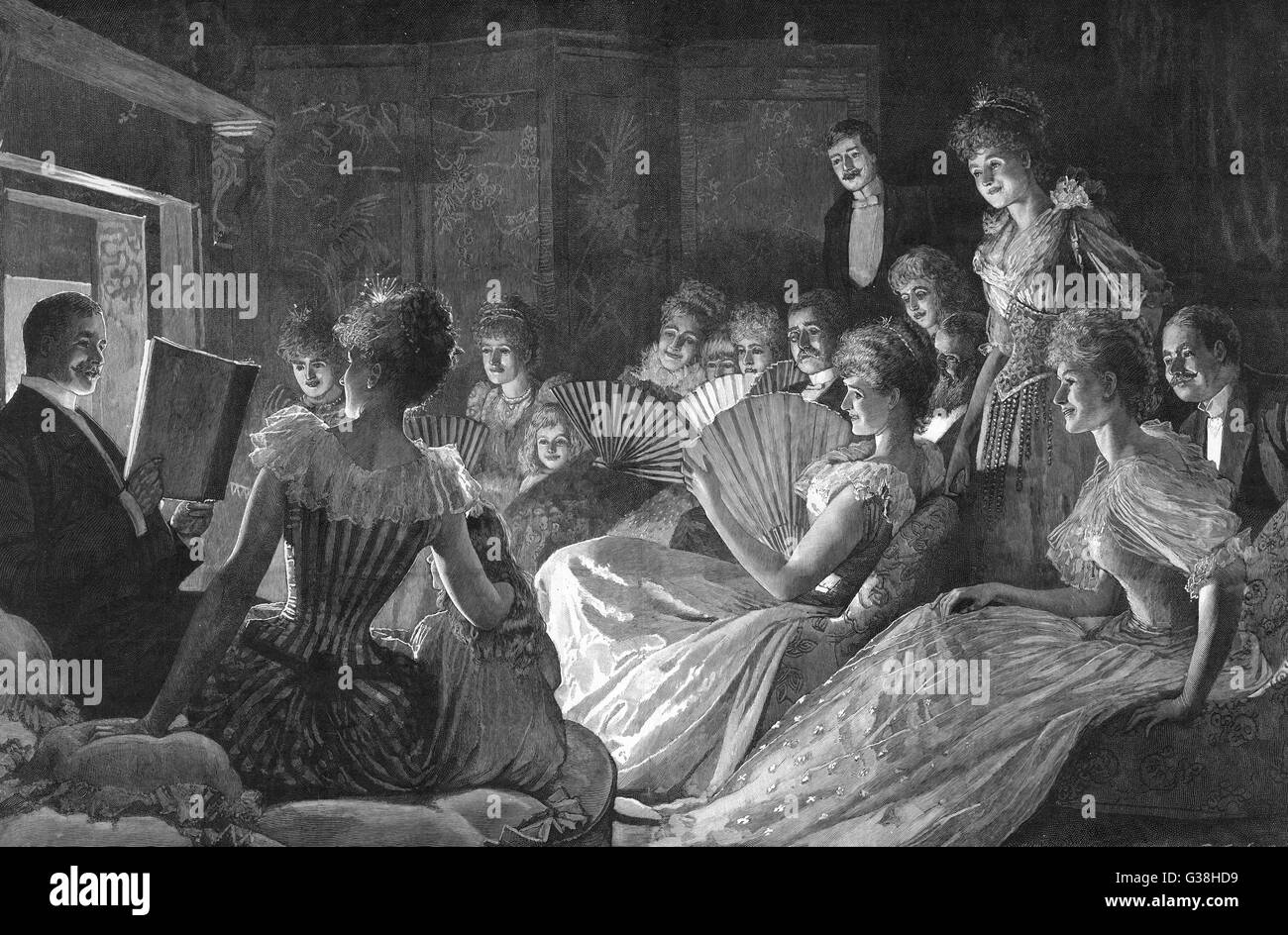 Reading a story to guests  at a Christmas house party         Date: 1892 - Stock Image
