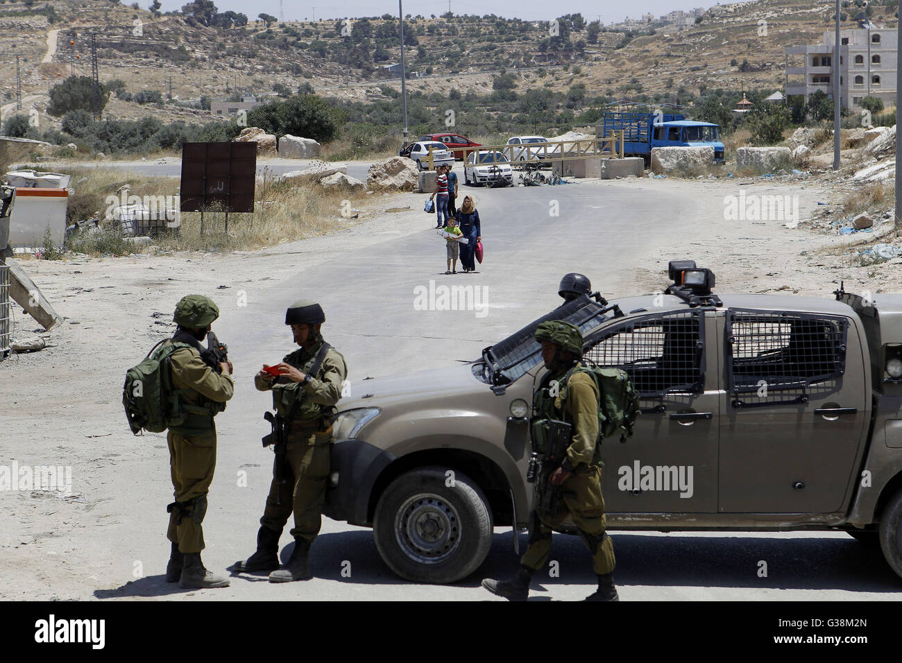 Hebron, West Bank, Palestinian Territory. 9th June, 2016. Israeli soldiers stand guard at the entrance of Yatta - Stock Image
