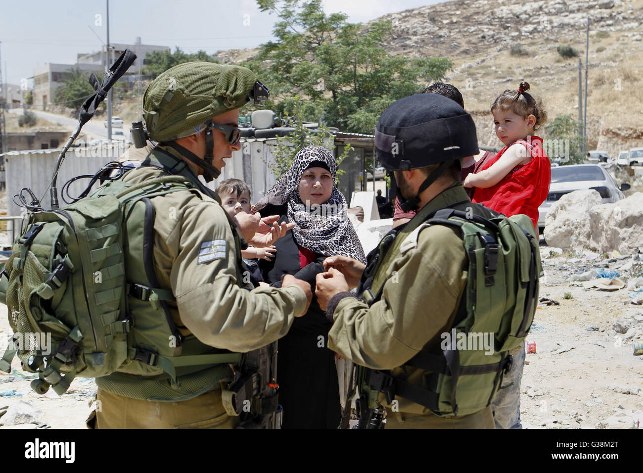 Hebron, West Bank, Palestinian Territory. 9th June, 2016. Israeli soldiers stop Palestinians at the entrance of - Stock Image