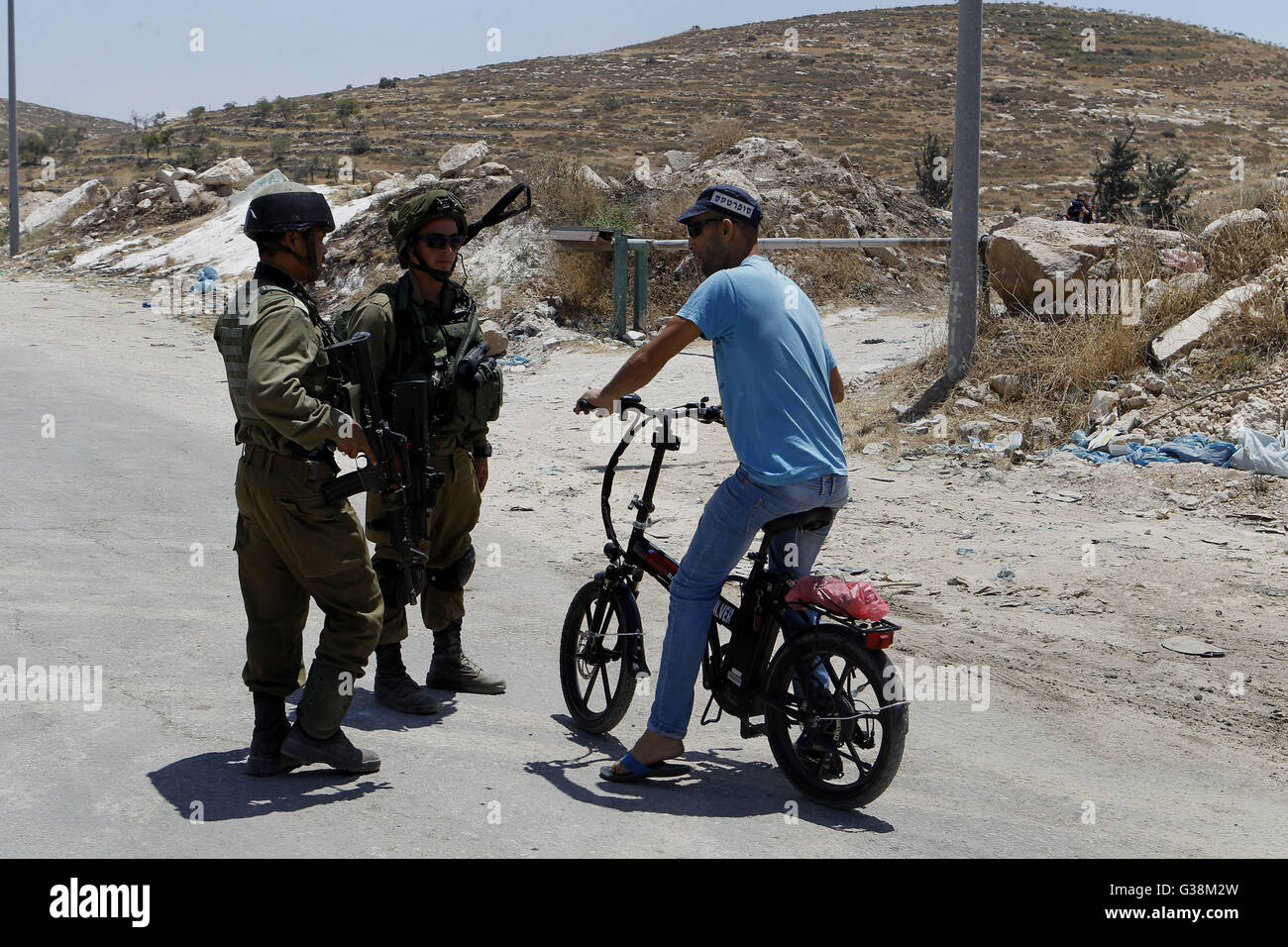 June 9, 2016 - Hebron, West Bank, Palestinian Territory - Israeli soldiers stop a Palestinian on his bicycle at - Stock Image