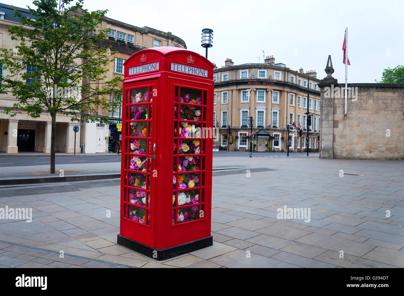 Traditional red telephone box filled with flowers - Stock Image