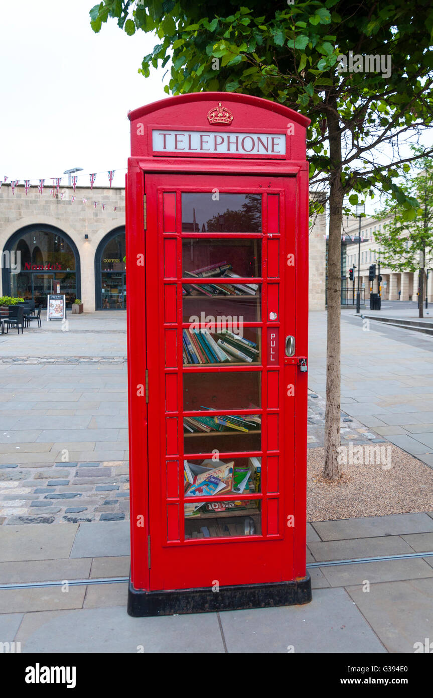 Traditional red telephone box filled books - Stock Image