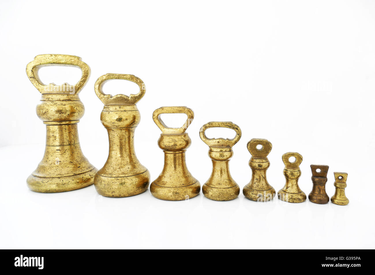 Old fashioned Imperial brass weights which were used on traditional scales,ranging from 4Lbs down to 1oz, pre metric. Stock Photo