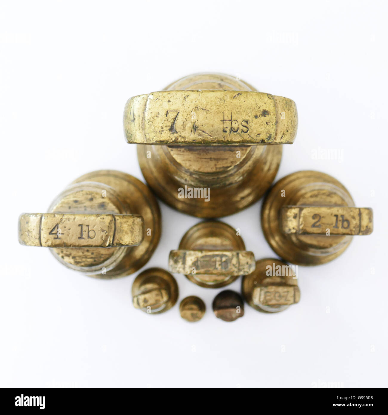 Old fashioned Imperial brass weights which were used on traditional scales,ranging from 4Lbs down to 1oz, pre metric. - Stock Image