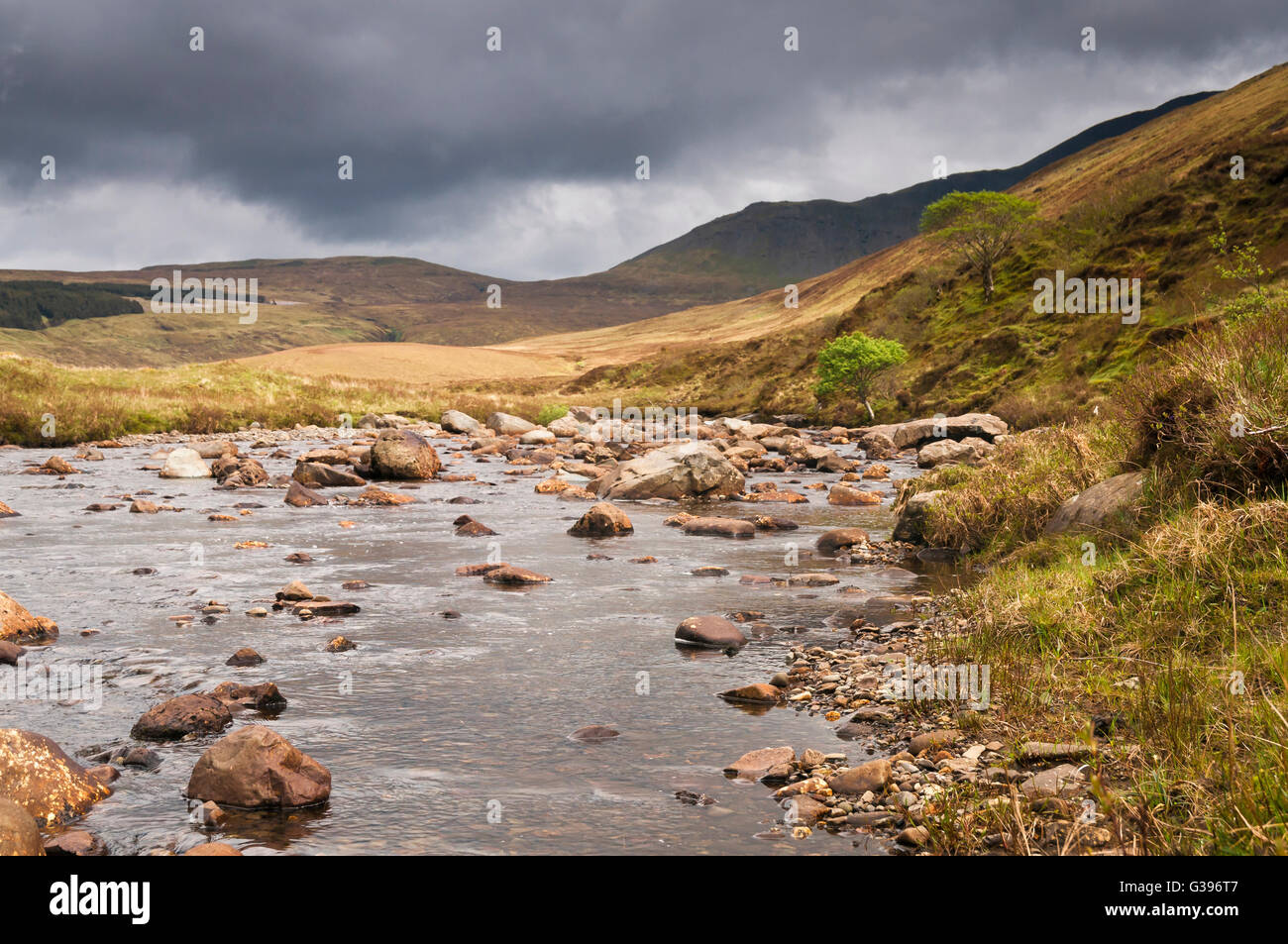A photograph looking up stream along the River Brittle with a threatening sky, on the Isle of Skye in Scotland. Stock Photo