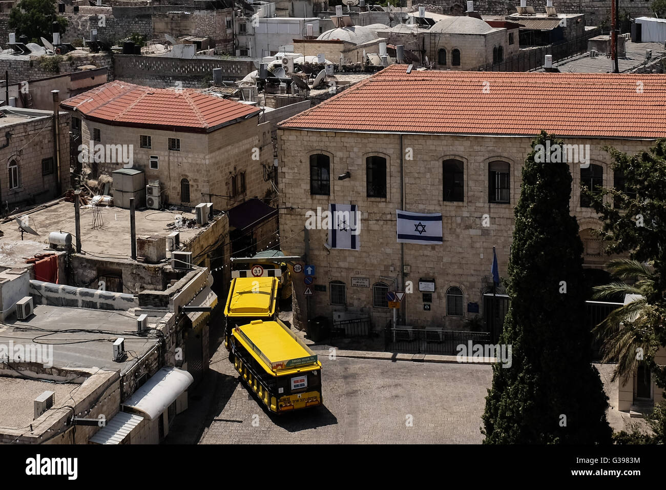 A tour train enters the Armenian Quarter left of the 'kishle' in Jerusalem's Old City. - Stock Image