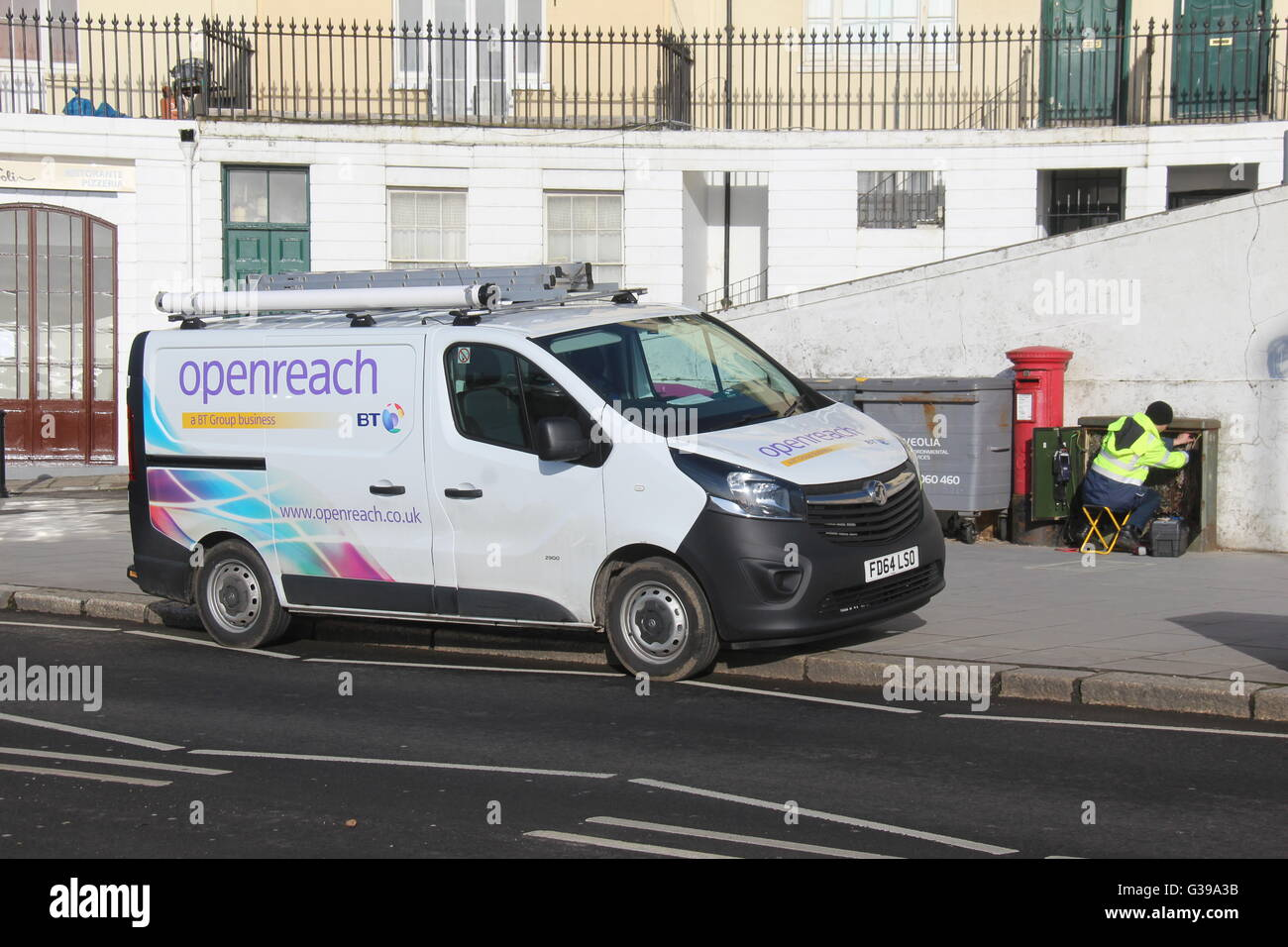 A BT OPENREACH VAUXHALL VIVARO VAN PARKED AT THE ROADSIDE WITH A TELEPHONE ENGINEER AT A GREEN BOX CARRYING OUT Stock Photo