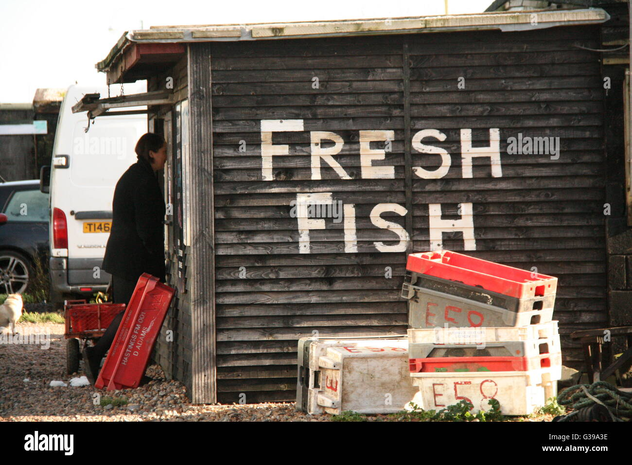 CUSTOMER BUYING FISH AT A WOODEN FRESH FISH HUT IN THE POPULAR RESORT OF HASTINGS - Stock Image