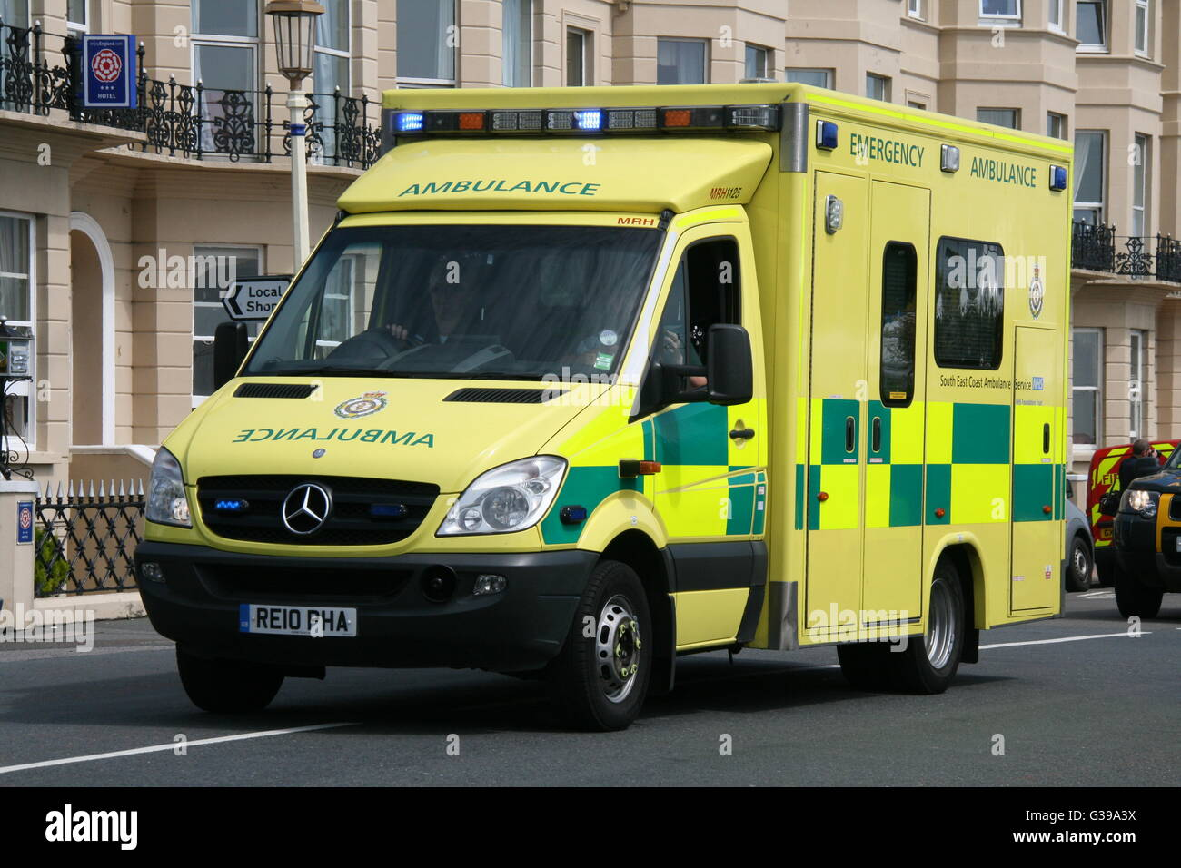 SOUTH EAST COAST AMBULANCE SERVICE MERCEDES AMBULANCE IN EASTBOURNE ON AN EMERGENCY CALL WITH BLUE LIGHTS FLASHING - Stock Image