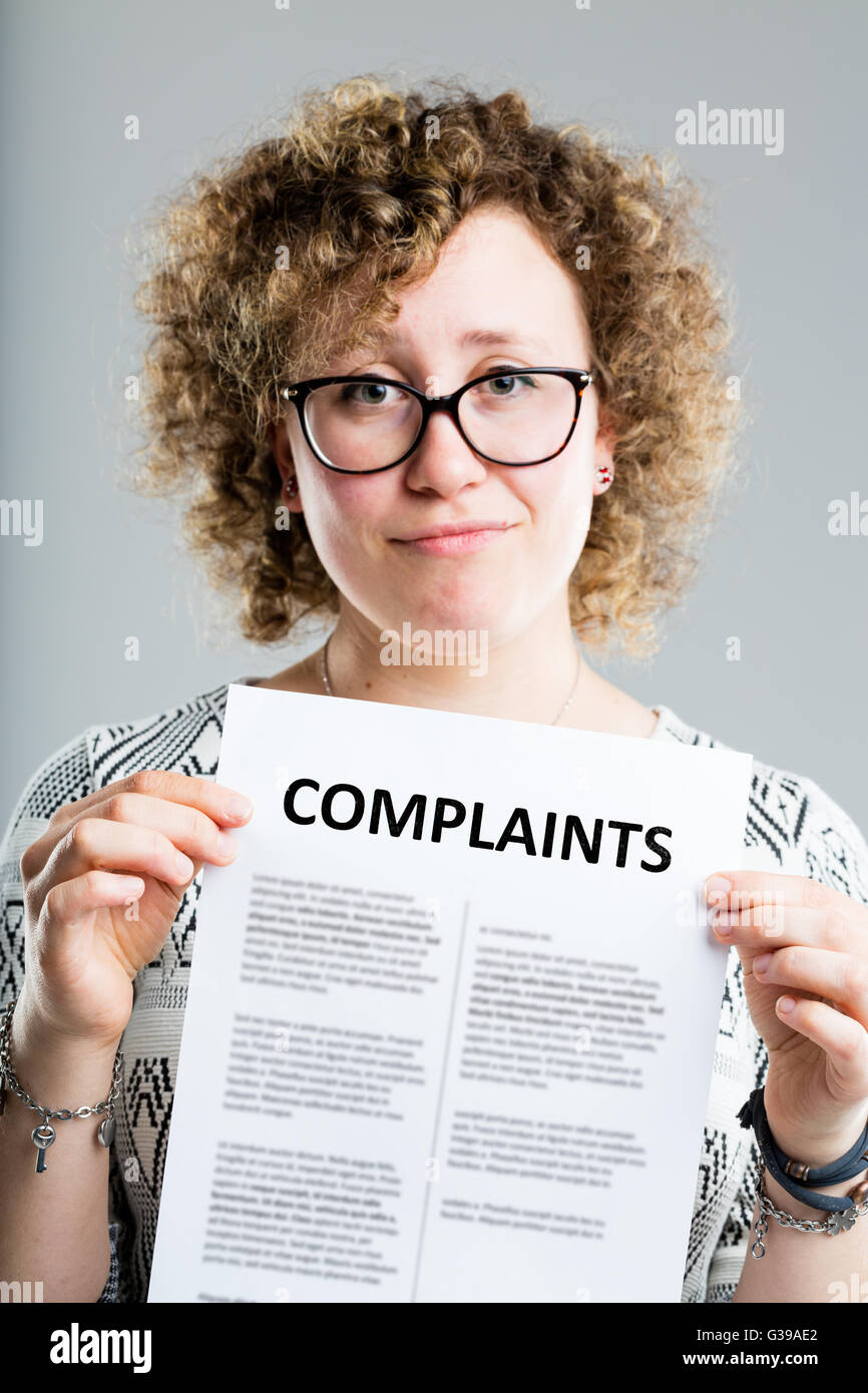 unhappy woman showing a complaints form she's about to send or she's just recceived - Stock Image