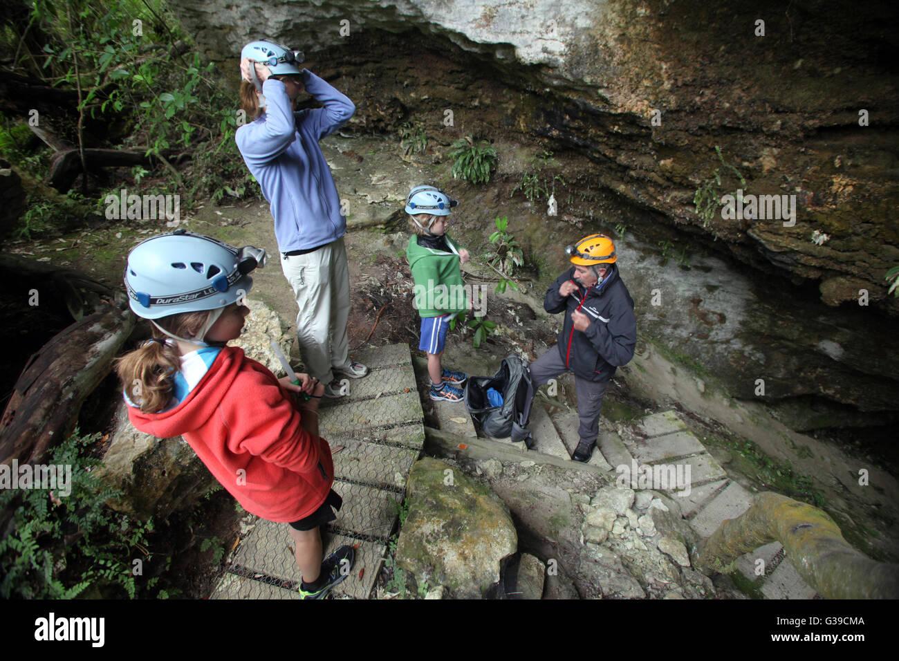 A family prepare to enter caves at Oparara, near Karamea, with a guide Stock Photo