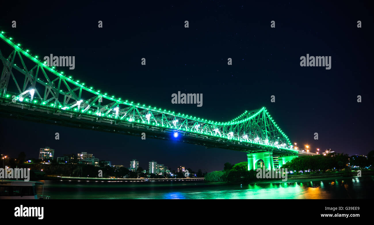 Story Bridge Brisbane Australia. Lighten up in green lighting with water reflection and star shining in the night - Stock Image