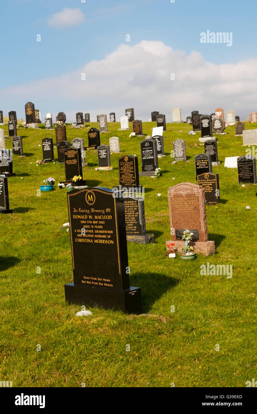 Headstones in a cemetery on the machair behind Luskentyre beach in South Harris on the Outer Hebrides. - Stock Image