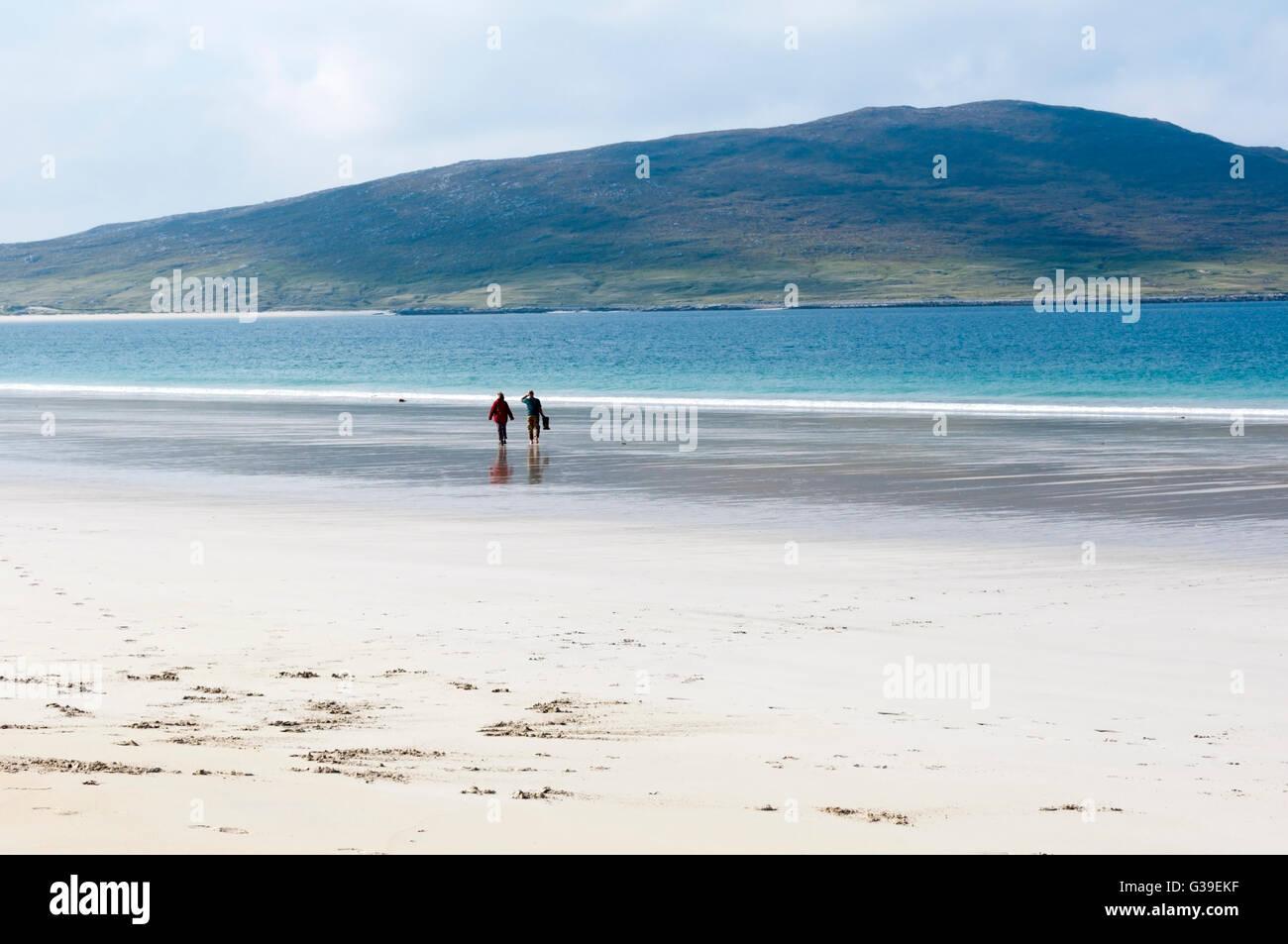 Couple walking on Luskentyre Beach on the west coast of the Isle of Harris. - Stock Image