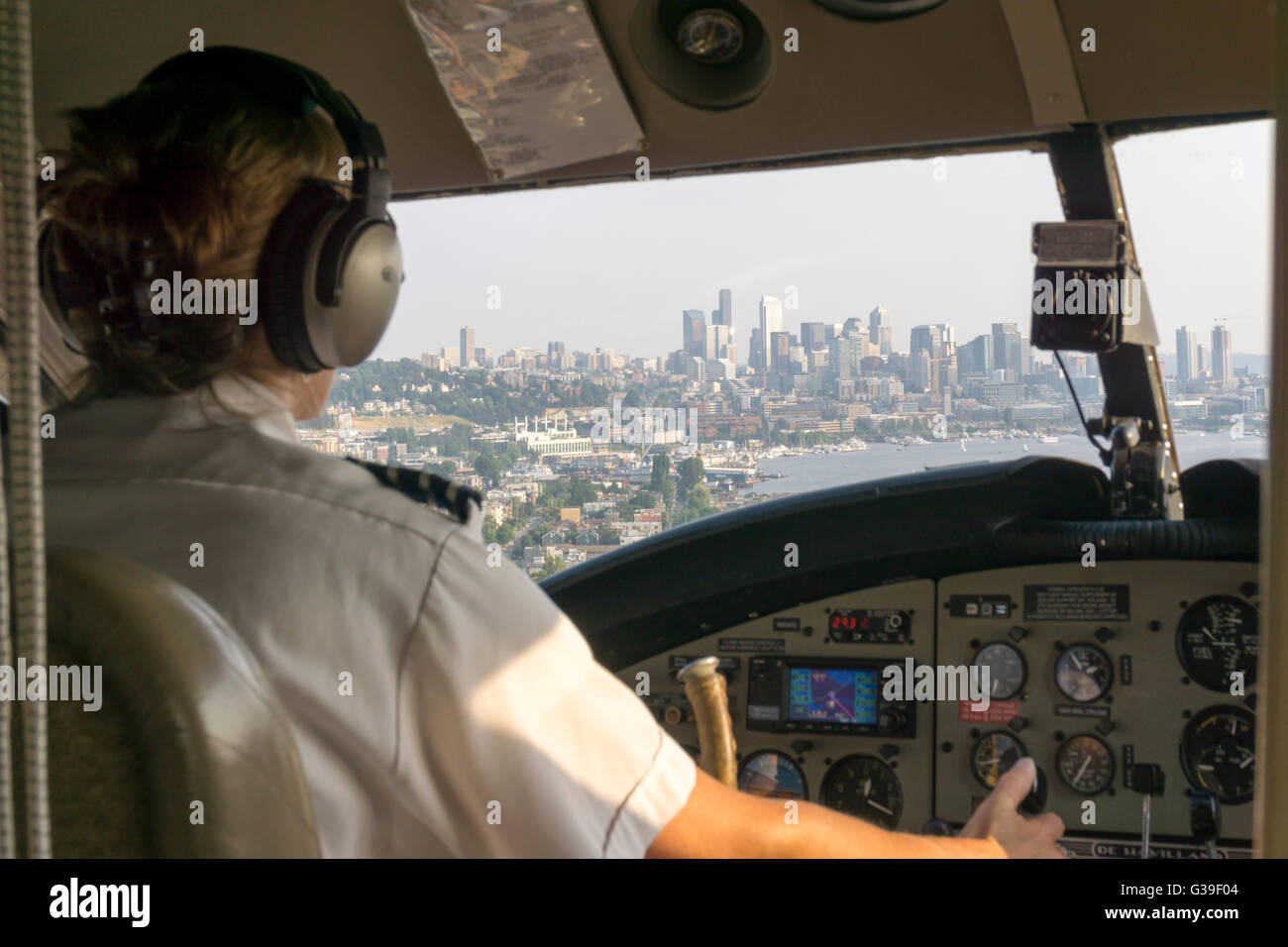 Female pilot of float plane coming in to land on Lake Union, Seattle with the city skyline seen through the cockpit - Stock Image