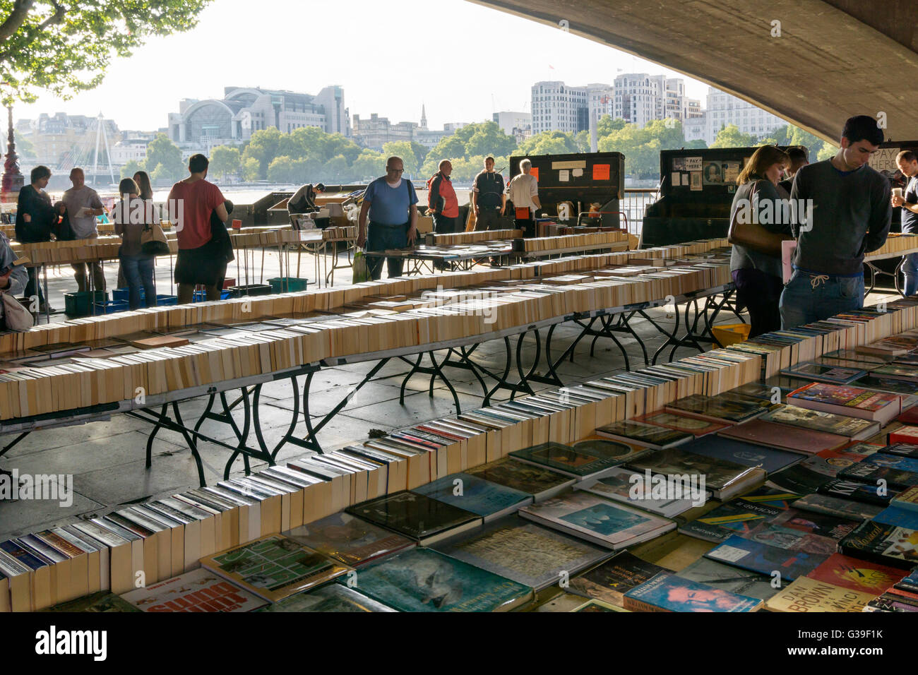 Locals and tourists browsing through the books at the Southbank book market under Waterloo Bridge, London. - Stock Image