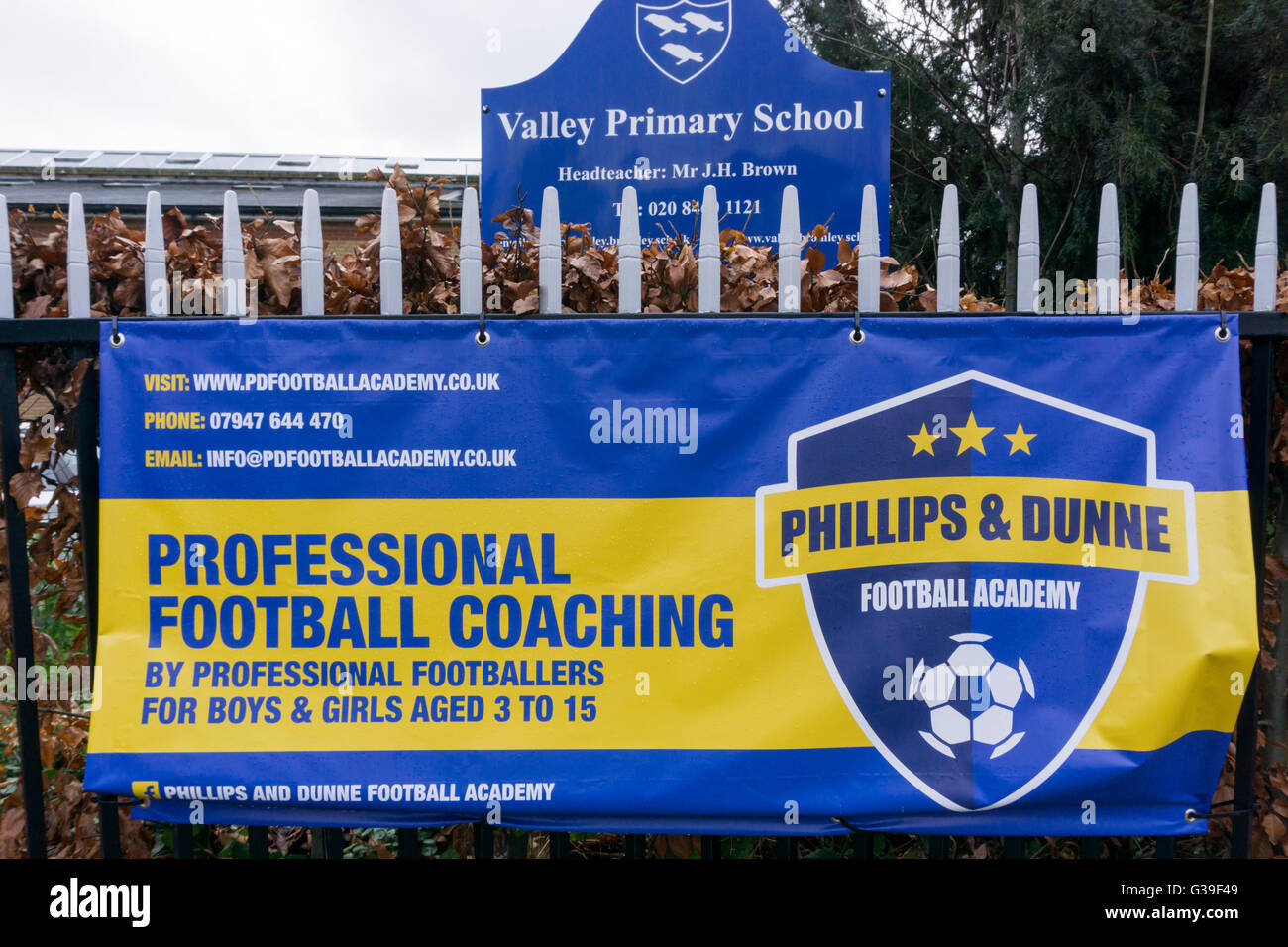 Professional Football Coaching sign for the Phillips and Dunne Football Academy outside a south London primary school. - Stock Image