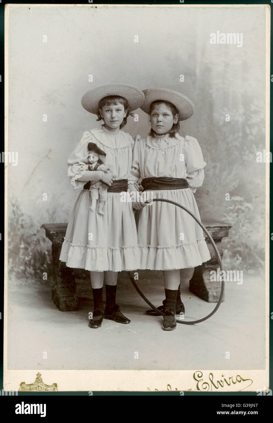 Two German girls in sailor  hats stand, one with her doll,  her sister with her hoop        Date: late 19th century - Stock Image