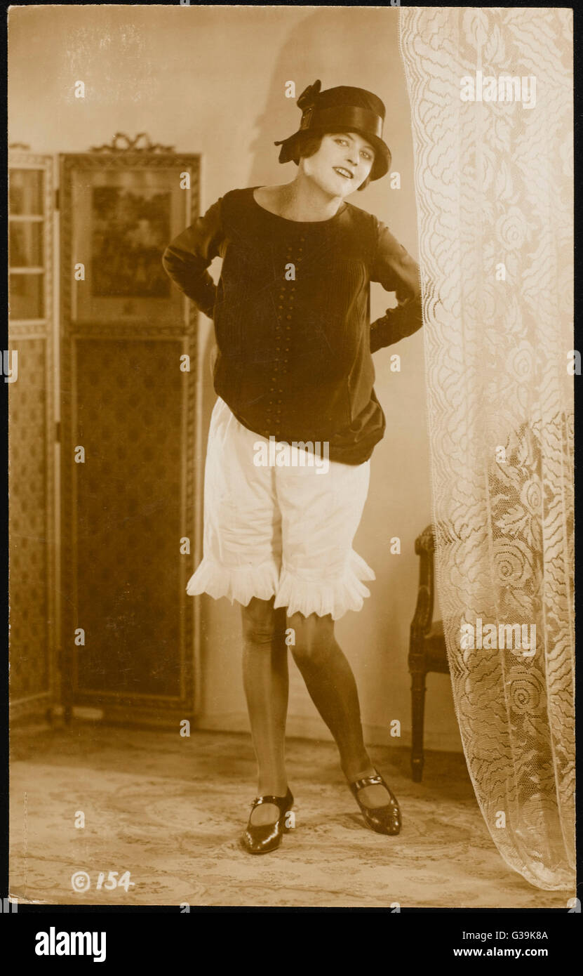 016998a60 A young woman lifts her dress to reveal lace edged pantaloons   bloomers.  She also wears a cloche hat