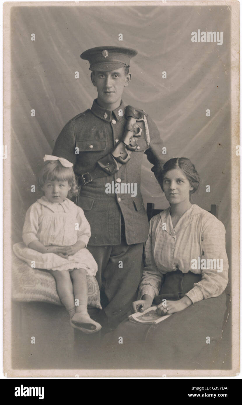 A soldier is photographed with  his wife and daughter before  leaving to fight for King and  Country       Date: - Stock Image