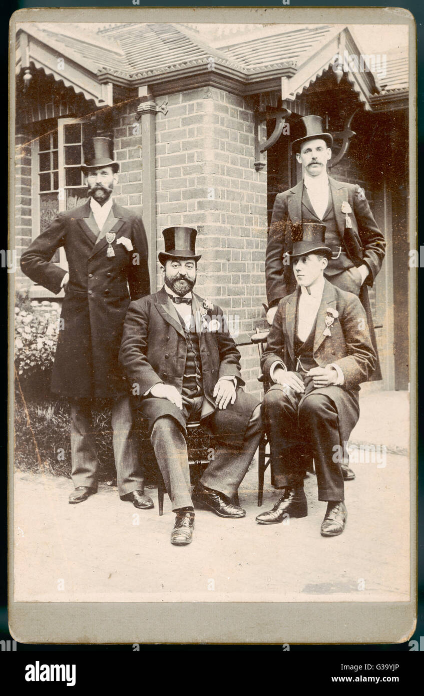 Four men, two seated, two  standing, in top hats and with  decorations pinned to their  lapels, pose for a photograph - Stock Image