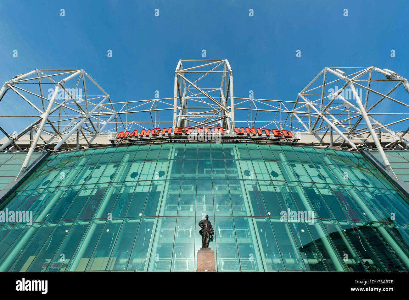 Old Trafford, the stadium of Manchester United Football Club, with the Sir Matt Busby statue on a sunny day (Editorial - Stock Image