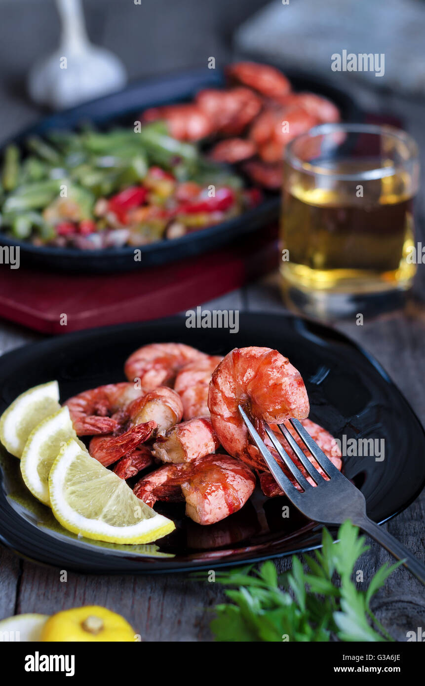 Grilled prawns with lemon, vegetables and beer. Rustic, low key and bokeh. - Stock Image