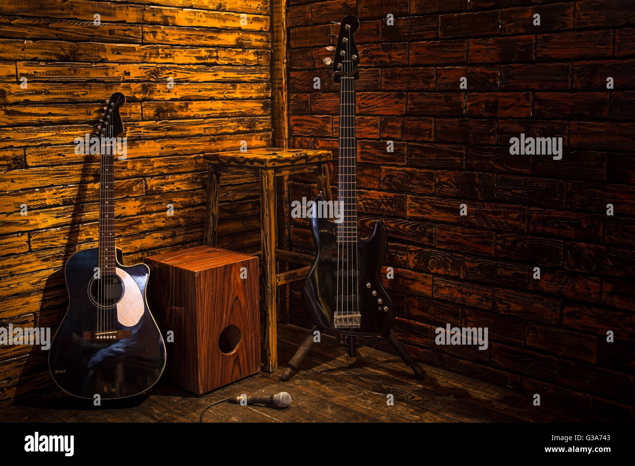 Cajon, bass and acoustic guitar on wooden stage in pub - Stock Image
