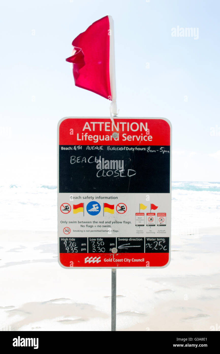 Sign warning that the beach is closed for swimming and surfing after a storm. - Stock Image