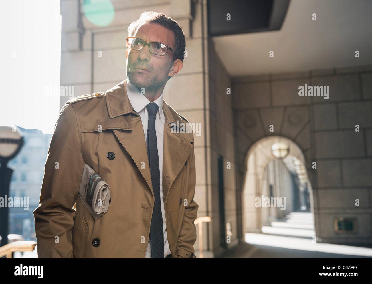 Corporate businessman in trench coat standing in sunny cloister - Stock Image