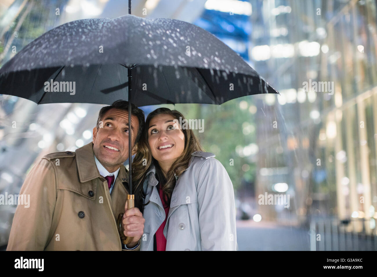 Businessman and businesswoman watching rain under umbrella Stock Photo