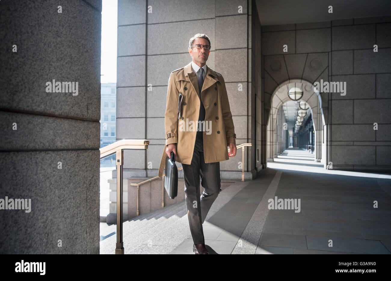 Corporate businessman in trench coat walking in cloister - Stock Image