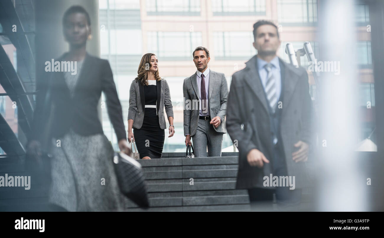 Corporate business people descending stairs - Stock Image