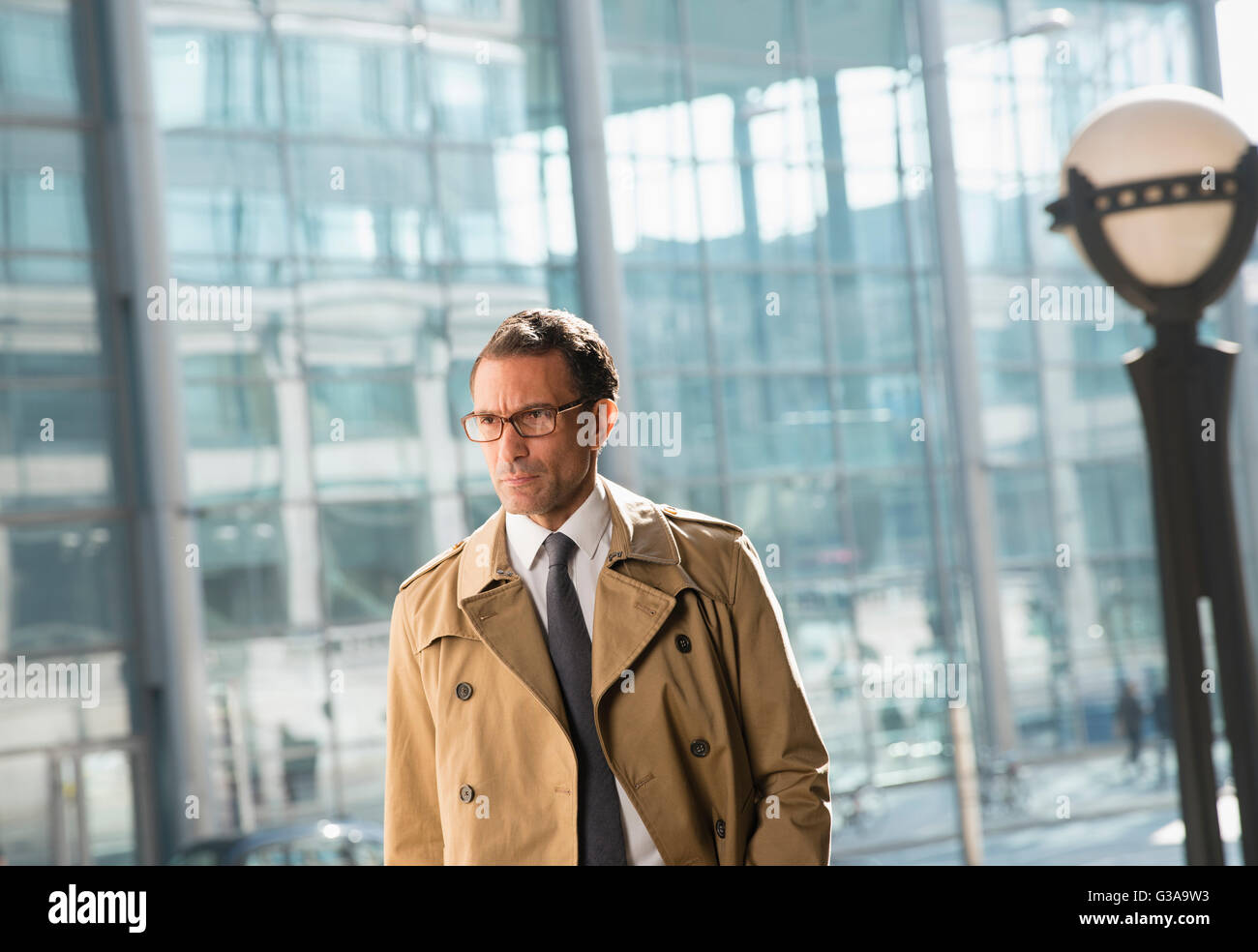 Corporate businessman in trench coat looking away - Stock Image