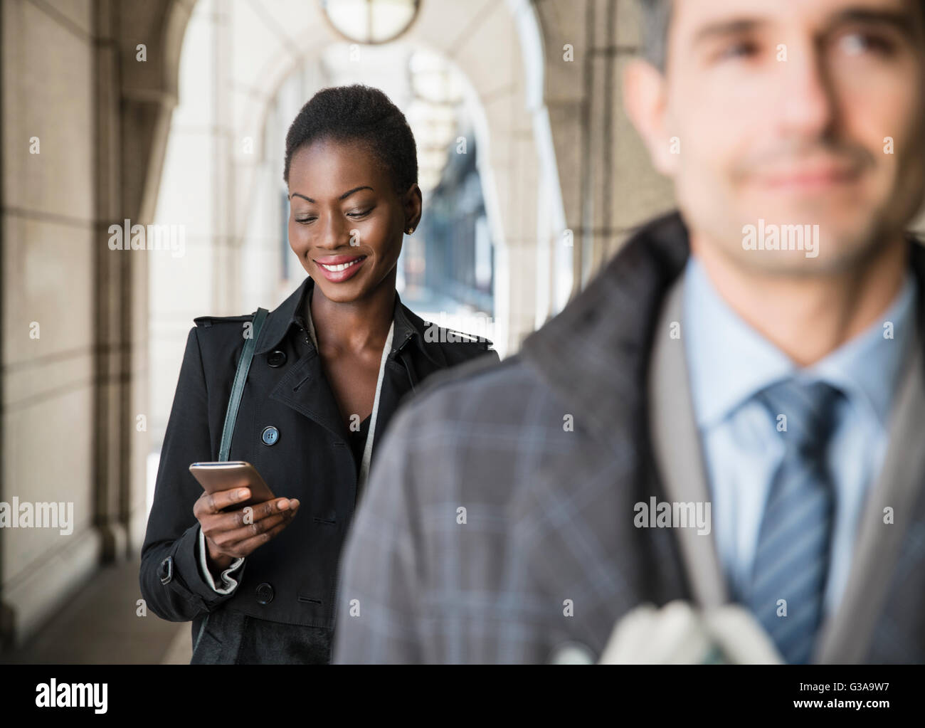 Corporate businesswoman texting with cell phone in cloister - Stock Image
