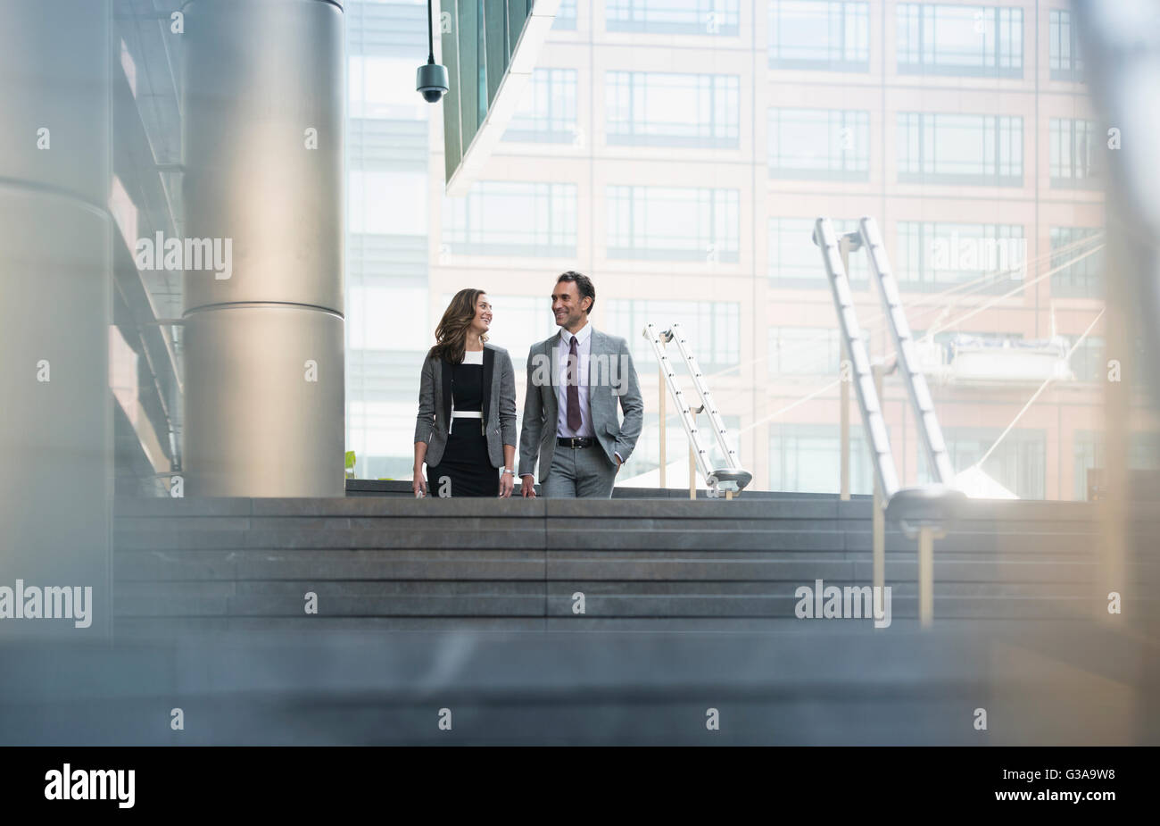Corporate businessman and businesswoman descending stairs outdoors - Stock Image