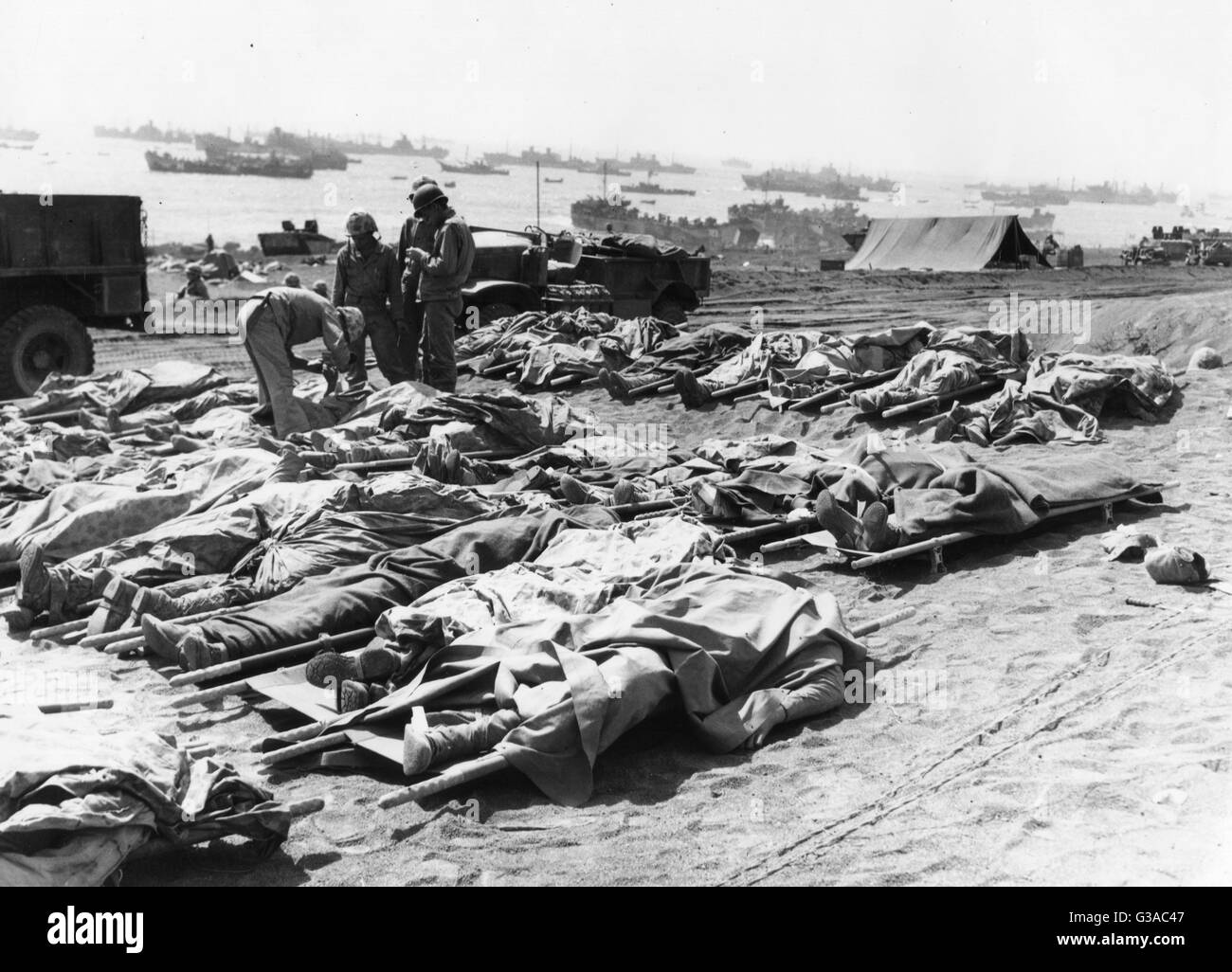 Dead Marines of the 3rd Marine Division, covered with their ponchos, lie on the beach after the battle of Iwo Jima. - Stock Image