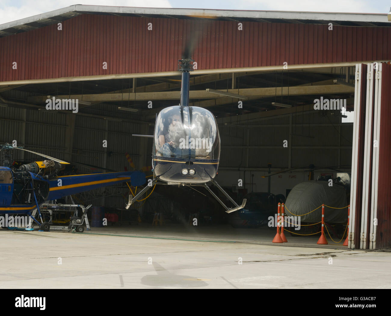 Two-bladed, single-engine light utility helicopter landing at a helicopter base - Stock Image