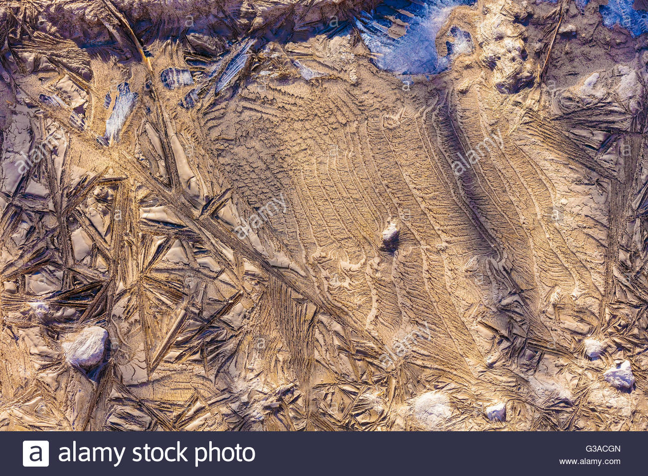 Abstract patterns formed as water saturated mud freezes in winter in Bluffer's Park in Toronto Ontario Canada - Stock Image