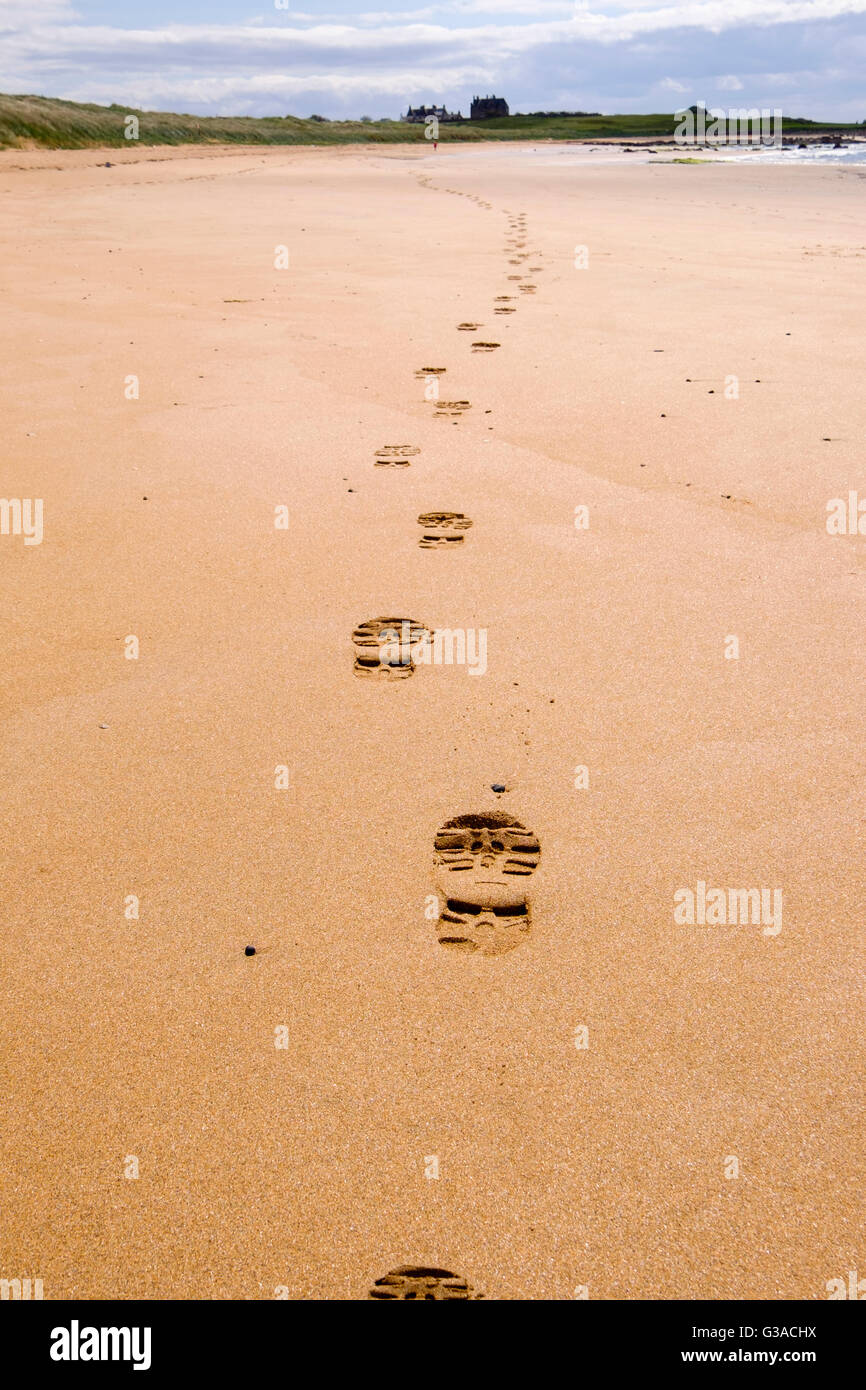 Line of footprints boot prints leading away in sand along Fife Coastal Path low tide route with walker in distance. - Stock Image
