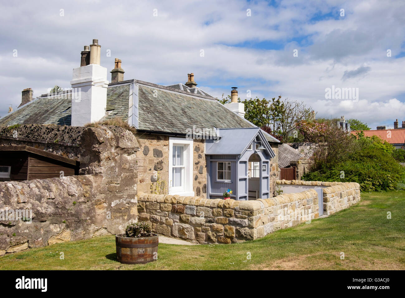 Quaint stone cottage with wooden porch and small walled front garden on seafront in village of Elie and Earlsferry - Stock Image