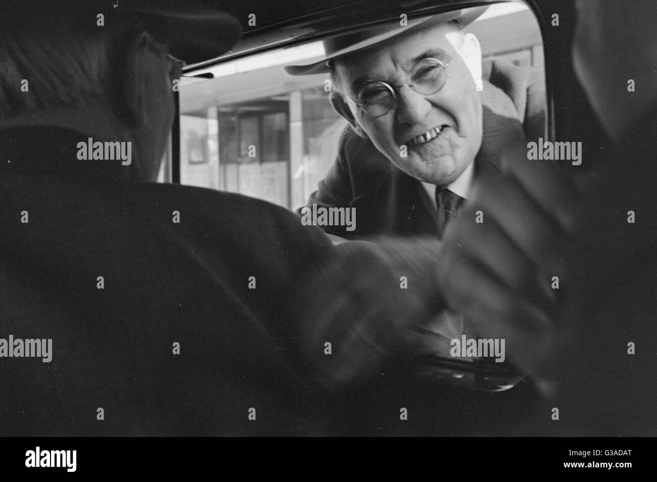 Man looking in through a car window     Date: late 1930s - Stock Image